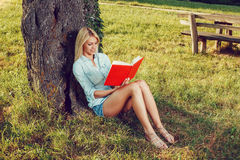 Young woman reading a book leaning on a tree Royalty Free Stock Image
