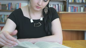 Young woman reading book at library stock video
