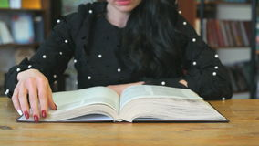 Young woman reading book at library stock video footage