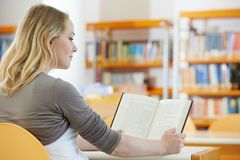 Young woman reading book in library Stock Image