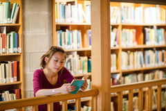 Young woman reading book in library Stock Photos