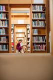 Young woman reading book in library Royalty Free Stock Photography