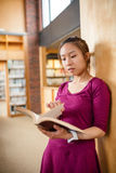 Young woman reading book in library Royalty Free Stock Photo