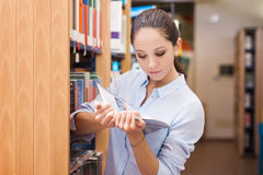 Young woman reading a book at the library Stock Image