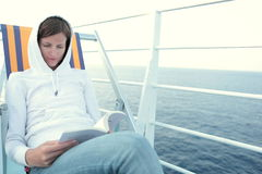 Young woman reading a book on a liner. Portrait of a young woman reading a book on a liner in the middle of a sea Stock Images