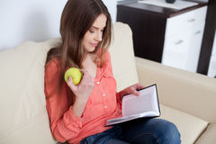 Young woman reading book in living room Royalty Free Stock Image