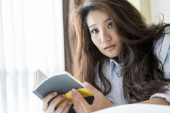 Young woman reading book while lying on the bed Royalty Free Stock Image