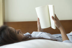 Young woman reading book while lying on the bed Stock Image