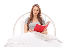 Young woman reading a book and lying in bed Stock Photo