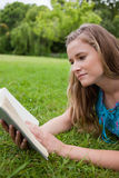 Young woman reading a book while lying down Royalty Free Stock Photos