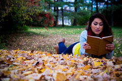 Young woman reading a book lying down on autumn leaves in the fa Royalty Free Stock Photos
