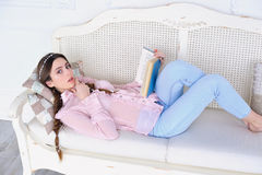 Young woman reading book. Young woman lying down on a sofa and reading a book Royalty Free Stock Photos