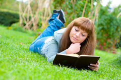 Young woman reading a book lying on the grass Stock Image