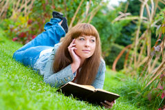 Young woman reading a book lying on the grass stock images