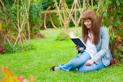 Young woman reading a book lying on the grass royalty free stock images