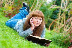 Young woman reading a book lying on the grass Royalty Free Stock Photo