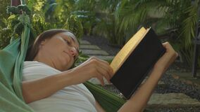 Young woman reading book lying in hammock on terrace. In slow motion stock video