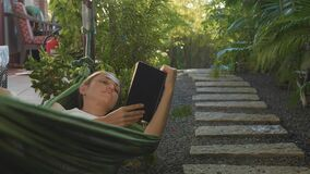Young woman reading book lying in hammock on terrace. In slow motion stock video footage