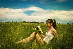 Young woman reading book on meadow Royalty Free Stock Photography