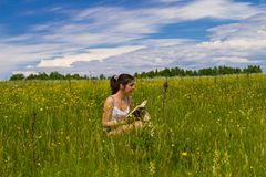 Young woman reading book on a meadow Stock Images