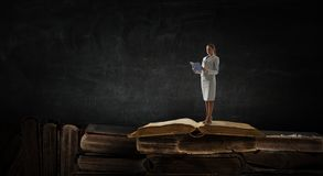 Young woman reading a book. Mixed media. Young businesswoman reading a book , close up vintage books on the background. Mixed media royalty free stock photo