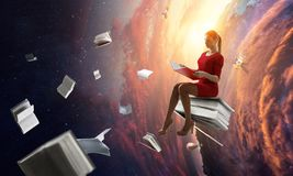 Young woman reading a book. Mixed media. Young woman in a red dress reading a book with other books flying around. Mixed media stock photo