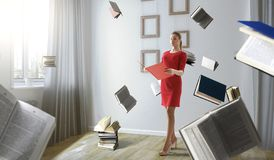 Young woman reading a book. Mixed media. Young woman in a red dress reading a book with other books flying around. Mixed media stock photography