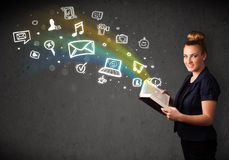 Young woman reading a book with multimedia icons coming out of t Royalty Free Stock Photos