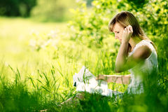 Young woman reading a book on nature, sitting on the grass in the park. Stock Image