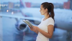 Young woman reading book near window at airport, blurred airplane on background. Girl tourist freelancer reads while waiting boarding at departure lounge stock video footage