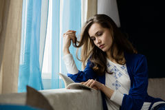 Young woman reading a book next to a window Stock Images