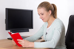 Young woman reading book in office Royalty Free Stock Photography