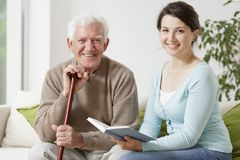 Young woman reading a book. Old men holding cane and young women reading a book Royalty Free Stock Photos