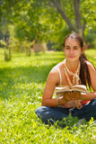 Young woman reading a book outdoors. Young attractive woman reading a book and sitting on a grass Royalty Free Stock Photo