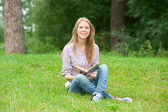 Young woman reading book outdoors Stock Photos
