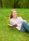 Young woman reading book outdoors Royalty Free Stock Image