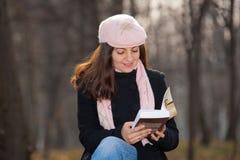 Young woman reading a book outdoors Stock Photos