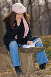 Young woman reading a book outdoors Royalty Free Stock Images