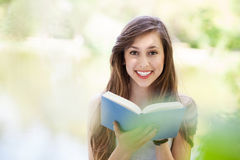 Young woman reading book outdoors Royalty Free Stock Images