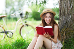 Young woman reading book outdoors Stock Images