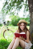 Young woman reading book outdoors Royalty Free Stock Photo