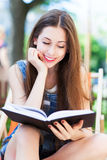 Young woman reading book outdoors Stock Photo