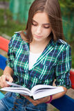 Young woman reading book outdoors. Beautiful young woman reading book outdoors in summer Stock Image