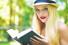 Young woman reading a book outside Stock Photo
