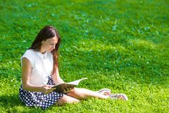 Young woman reading a book outside in park Stock Photos