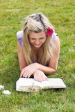 Young woman reading a book in a park Stock Photos