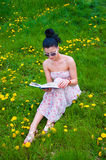Young woman reading a book in the park Royalty Free Stock Photo