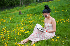 Young woman reading a book in the park Stock Images