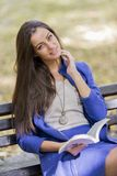 Young woman reading book in the park. Young woman reading a book in the park Royalty Free Stock Photo