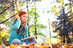 Young woman reading a book in park Royalty Free Stock Photos